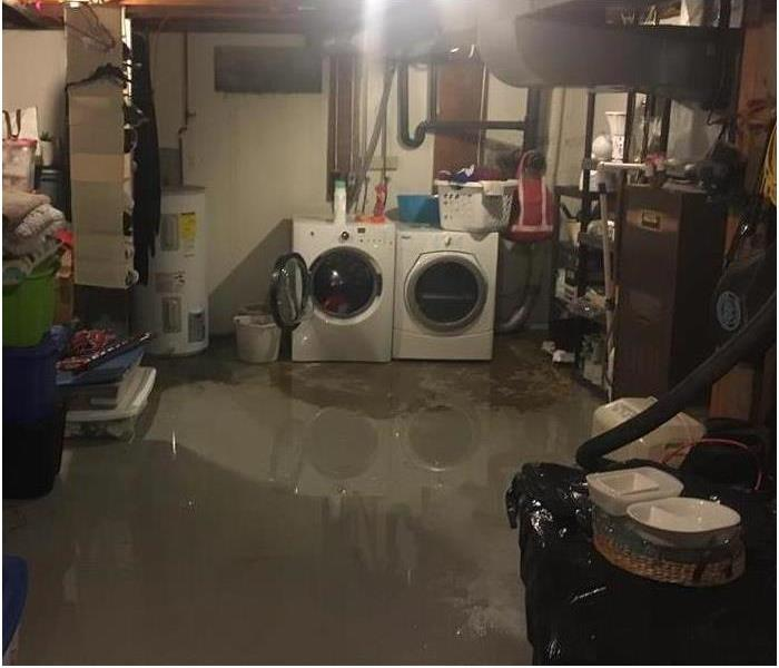 flooded basement with concrete flooring covered in water