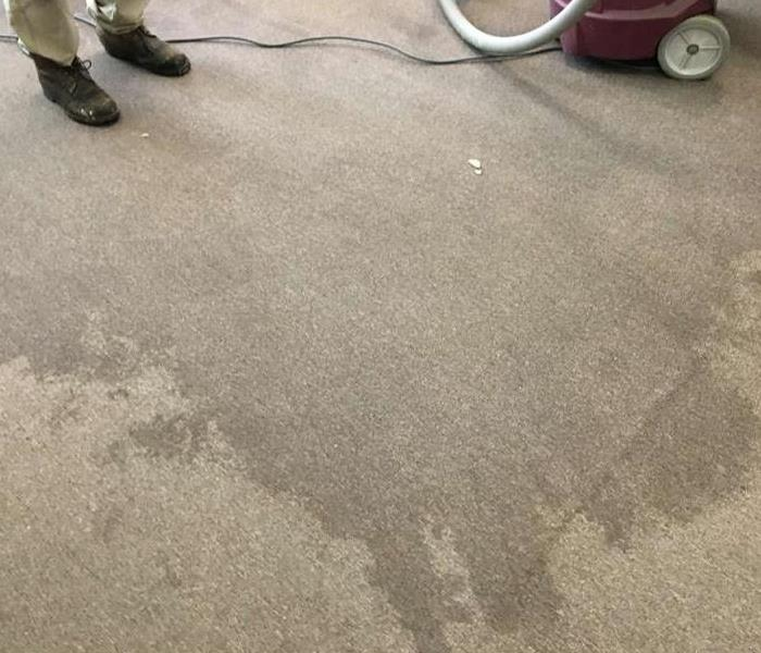 water stained carpet with machine and hose on right and someone standing on left with only boots showing